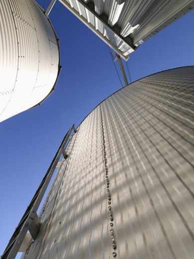 Low angle view of metal grain storage silos against blue sky. : Stock Photo