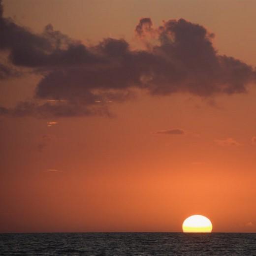 Stock Photo: 4029R-57174 Sun setting over horizon of ocean.