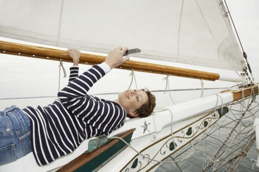 Stock Photo: 4029R-57746 Mid adult woman lying on boat s bow and text messaging