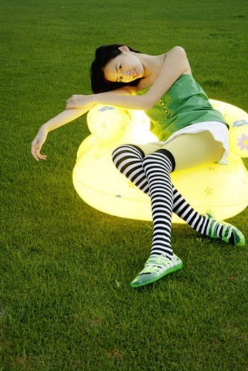 Young woman sitting on yellow lighting air chair : Stock Photo
