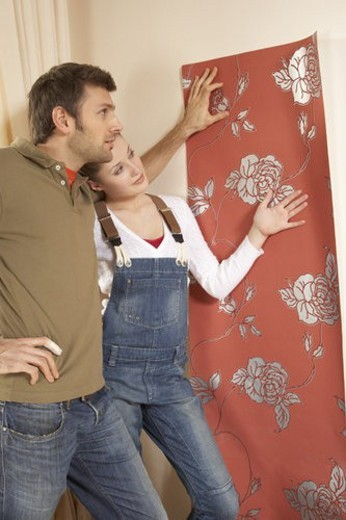 Young couple fixing wallpaper on a wall : Stock Photo
