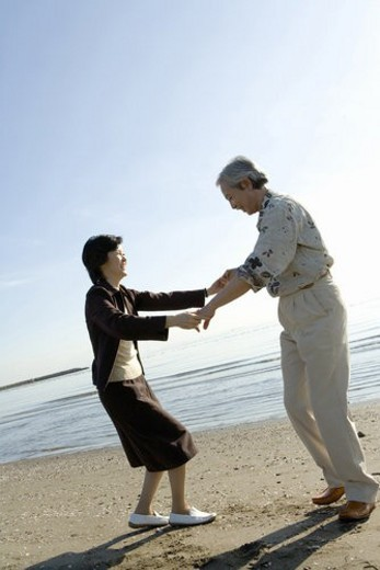 A Mature Couple Enjoying on the Beach, Side View, Full Length : Stock Photo