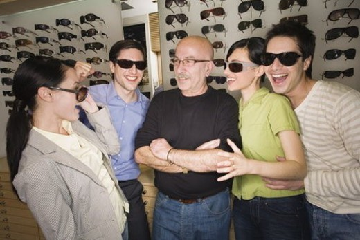 Stock Photo: 4029R-62232 Two couples posing with sunglasses in store with shopkeeper