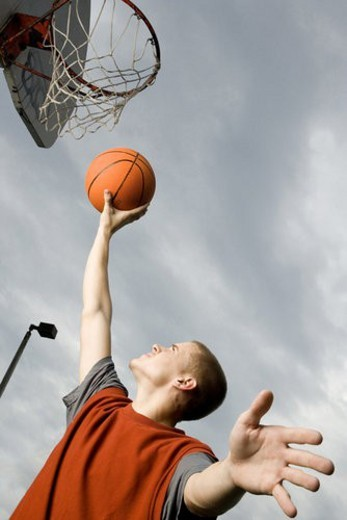 Stock Photo: 4029R-6257 A teenage boy playing basketball