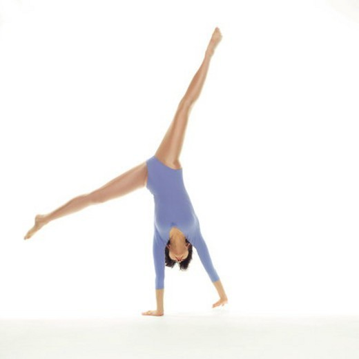 Stock Photo: 4029R-6387 A woman in Leotard doing handstand, Front View, Copy Space