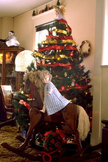 Stock Photo: 4029R-6404 Doll riding rocking horse beside Christmas tree