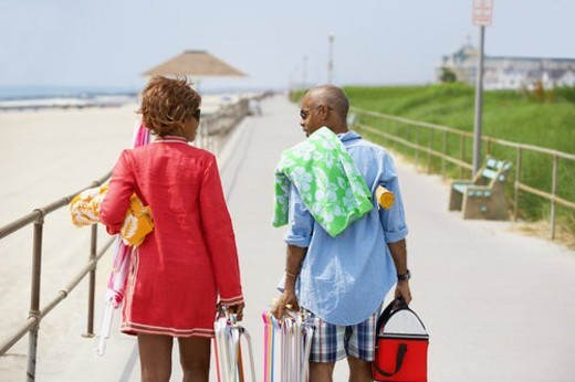 Man and woman carrying picnic equipment at beach (rear view), Spring Lake, New Jersey, USA : Stock Photo