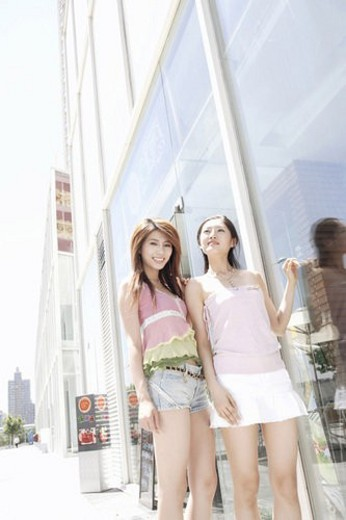 Two young women standing in front of glass window : Stock Photo