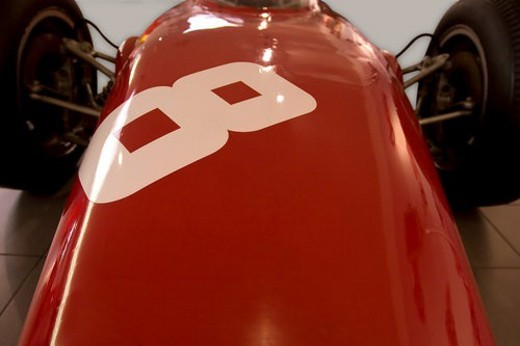 Detail of red Ferrari, race car, front view of hood and rear wheels, number 8 on hood : Stock Photo