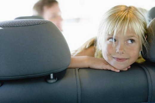 Portrait of girl in car, smiling and looking away : Stock Photo