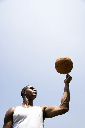 Young African American man spinning a basketball on his finger : Stock Photo