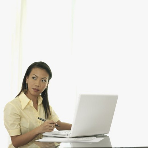 Businesswoman sitting in front of a laptop : Stock Photo