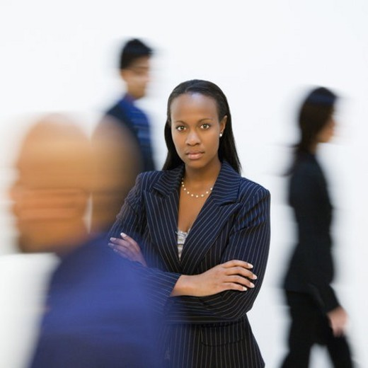 African-American businesswoman standing with arms crossed while others walk by. : Stock Photo