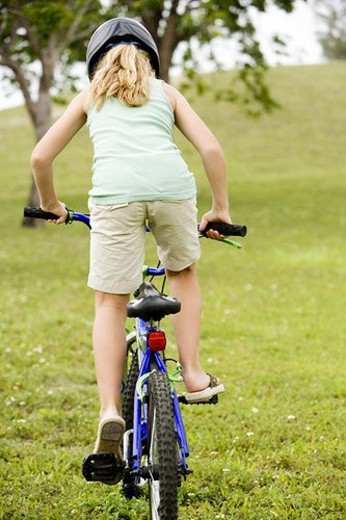 Stock Photo: 4029R-71762 girl riding bicycle on the grass