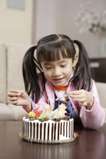 Girl lighting candles on cake : Stock Photo