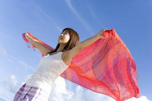 Stock Photo: 4029R-71996 Woman holding fabric behind back on beach, smiling, Saipan, USA