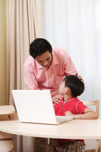 Father talking with son in front of laptop : Stock Photo