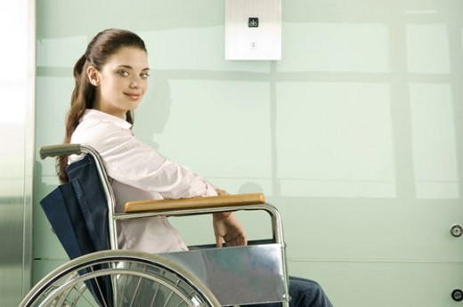 A woman in a wheelchair waiting for the lift : Stock Photo