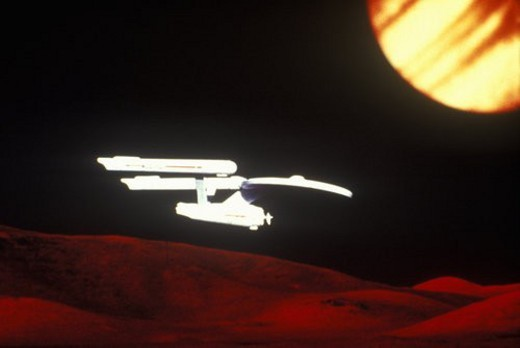 Star Trek s USS Enterprise soars over and alien landscape : Stock Photo