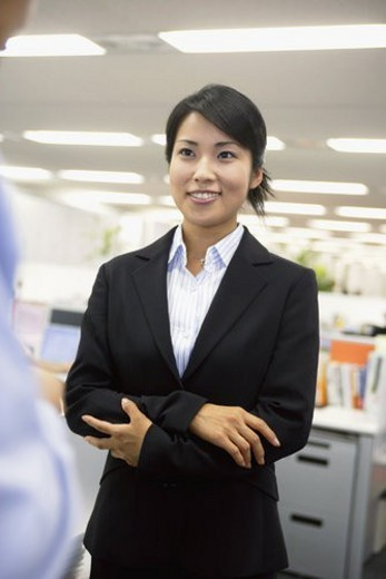 A formally dressed woman gives a smile at her colleague : Stock Photo