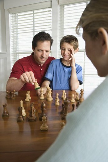 Stock Photo: 4029R-73075 Caucasian mid-adult mother watching mid-adult dad teaching chess to pre-teen son.