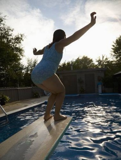 Stock Photo: 4029R-75984 Girl on diving board over swimming pool