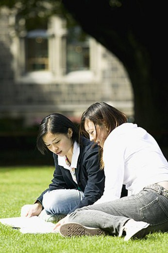 Two young women sitting on lawn : Stock Photo