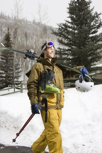Attractive man in winter clothing walking in snow carrying ski equipment and smiling. : Stock Photo
