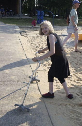 Girl with a disability using canes for mobility assistance leaving the playground after having a really good time. : Stock Photo