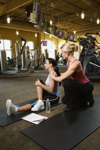 Prime adult Caucasian female with personal trainer at gym. : Stock Photo