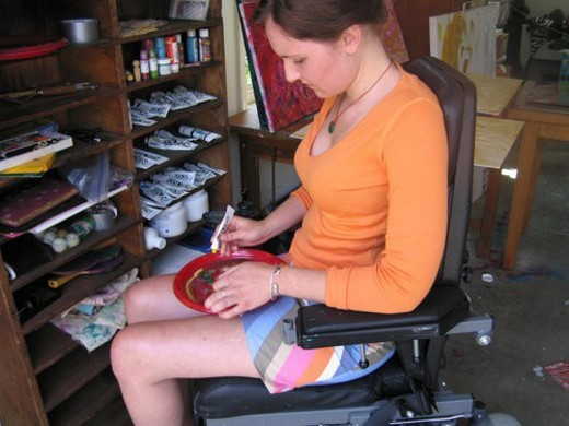 Young woman (wheelchair user) mixes paint in her art studio. : Stock Photo