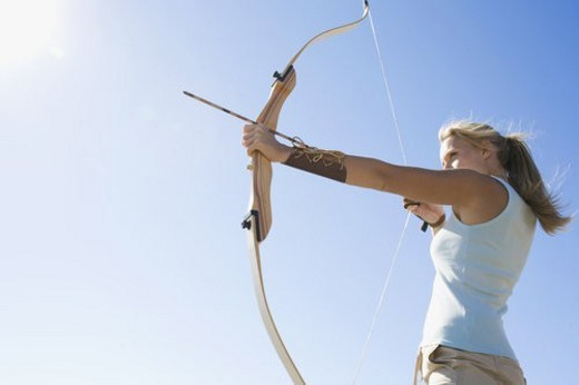 Stock Photo: 4029R-77226 Young woman arrow shooting (low angle view)