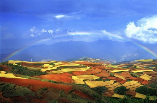Rainbow over red soil area : Stock Photo