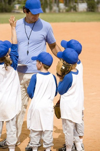 Stock Photo: 4029R-78233 Youth league baseball team and coach on pitch