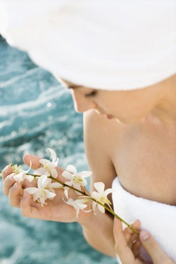 Pretty Caucasian mid-adult woman wearing towel on head holding flowers beside pool. : Stock Photo
