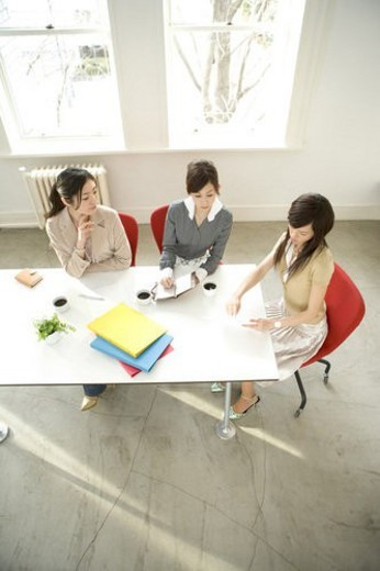 Three women having meeting at desk : Stock Photo