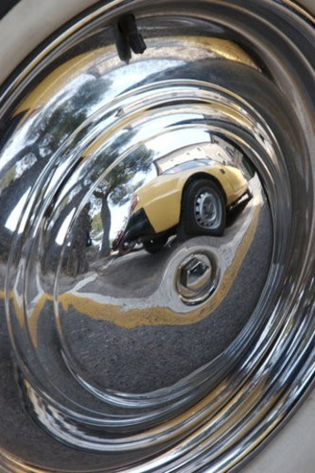 Reflection of antique yellow car and Italian castle, reflected in wheel hub  of antique car : Stock Photo