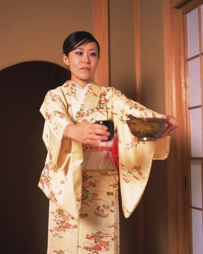 Woman in kimono standing and holding Japanese cups in a tea room, front view, Japan : Stock Photo