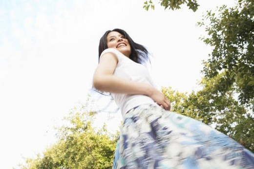 Stock Photo: 4029R-81339 Happy young woman being playful at the park