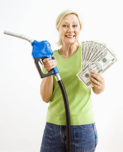 Portrait of smiling adult blonde woman holding gas nozzle and lots of money. : Stock Photo