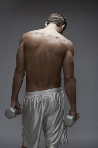 Mid adult man holding dumbbells (rear view) : Stock Photo