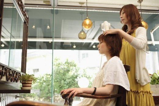 Hairdresser drying woman s hair : Stock Photo