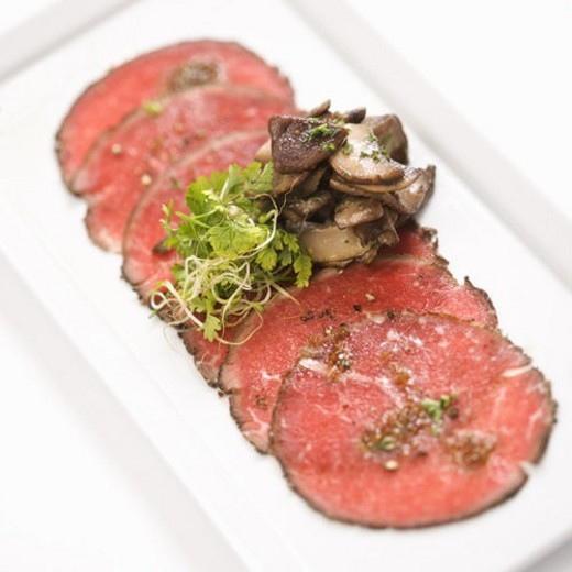 Pepper charred beef carpaccio with mushrooms. : Stock Photo