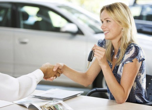 A young woman buying a new car : Stock Photo