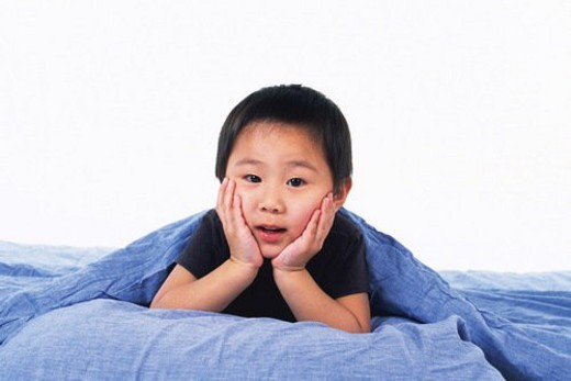 Little Boy resting his chin on his hands Under a Blue Blanket, looking at camera, Front View : Stock Photo