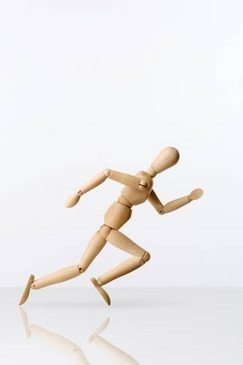 Wooden figure running on white background : Stock Photo