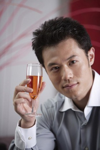 Young man holding a glass of champagne : Stock Photo