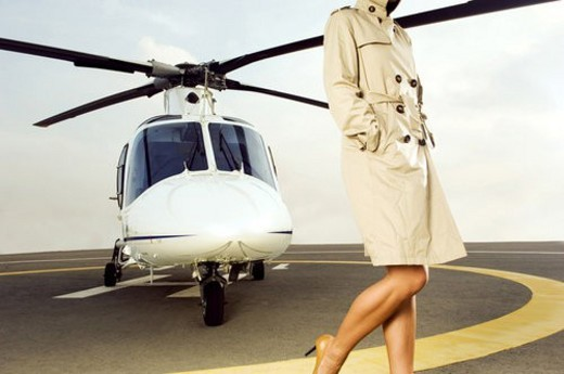 A woman standing by a helicopter : Stock Photo