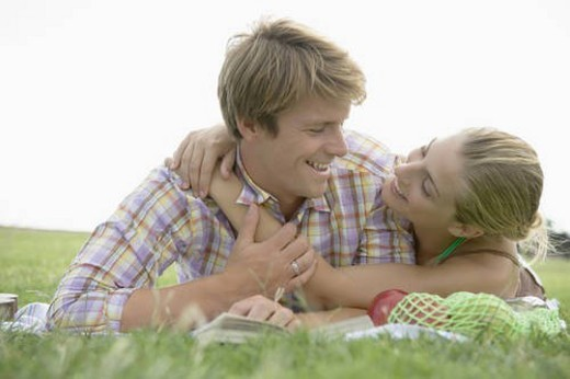 Young Couple Cuddling and Lying on Grass : Stock Photo