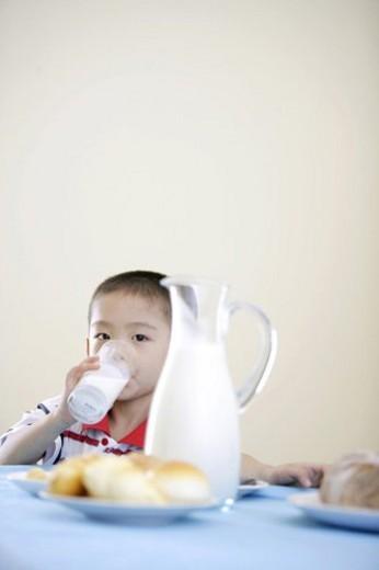 Stock Photo: 4029R-87304 Boy drinking milk behind bread